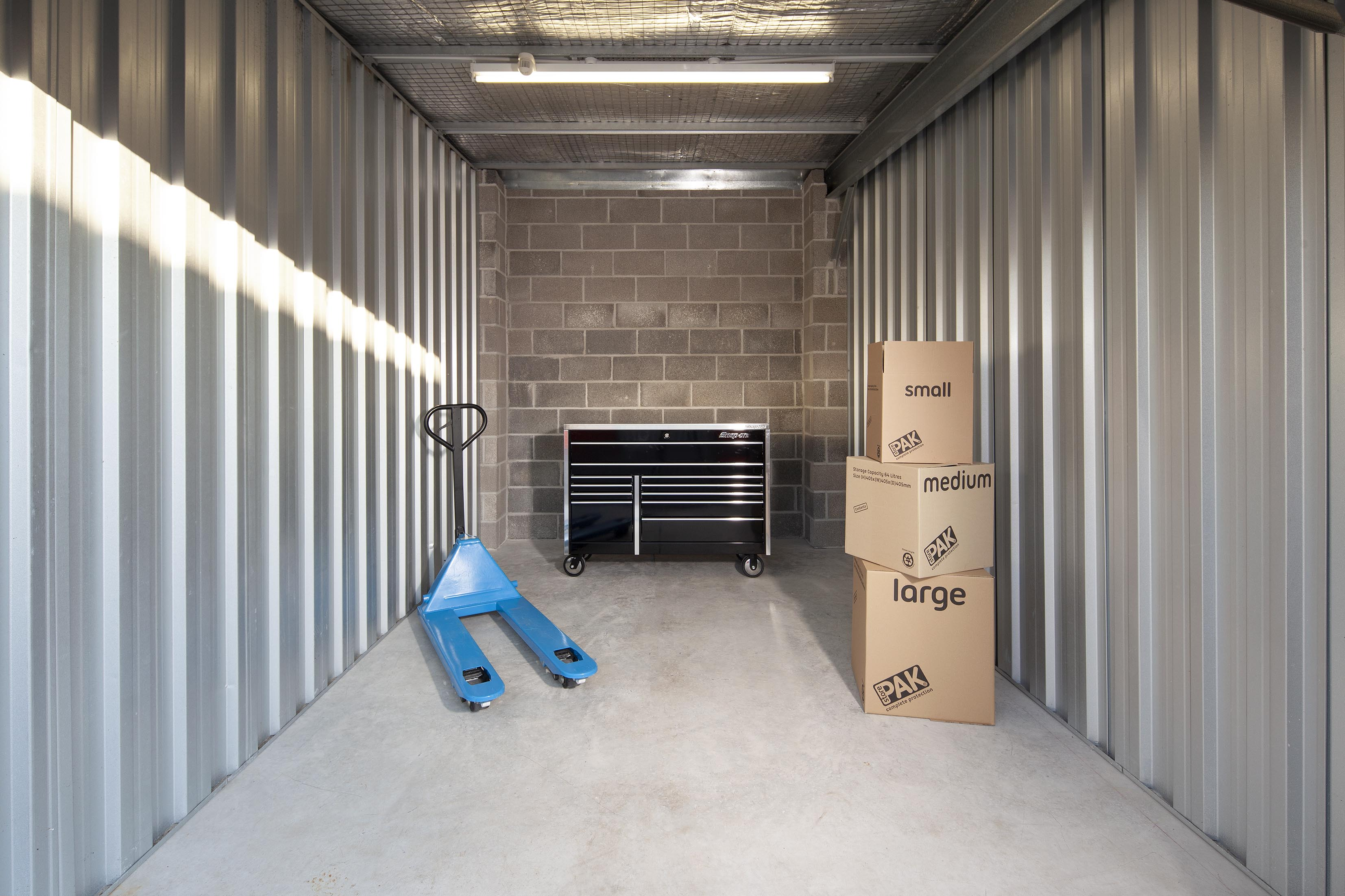 140 ft storage unit with mobile tool trolly, boxes and a pallet mover.